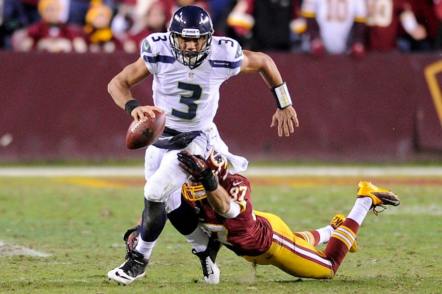 Seattle Seahawks quarterback Russell Wilson (3) is sacked by Washington Redskins strong safety Reed Doughty (37) in the fourth quarter of the NFC wild card game at FedEx Field, Landover, Md., Jan. 6, 2013. (Preston Keres/Special to The Washington Times)