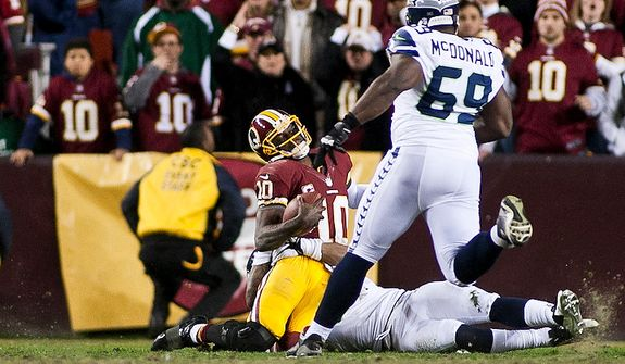 Washington Redskins quarterback Robert Griffin III (10) is hit hard in the fourth quarter and is later taken out with an injury to his knee against the Seattle Seahawks in the NFC wild card game at FedEx Field, Landover, Md., Sunday, January 6, 2013. (Craig Bisacre/The Washington Times)