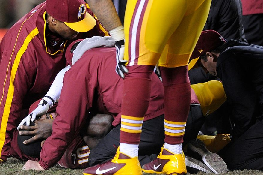 Washington Redskins quarterback Robert Griffin III (10) lies injured on the field as trainers look at his knee in the fourth quarter of the NFC wild card game at FedEx Field, Landover, Md., Jan. 6, 2013. (Preston Keres/Special to The Washington Times)