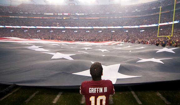 Local firefighters hold a giant American flag for the national anthem before the start of the Washington Redskins against the Seattle Seahawks in the NFC wild card game at FedEx Field, Landover, Md., Sunday, January 6, 2013. (Craig Bisacre/The Washington Times)