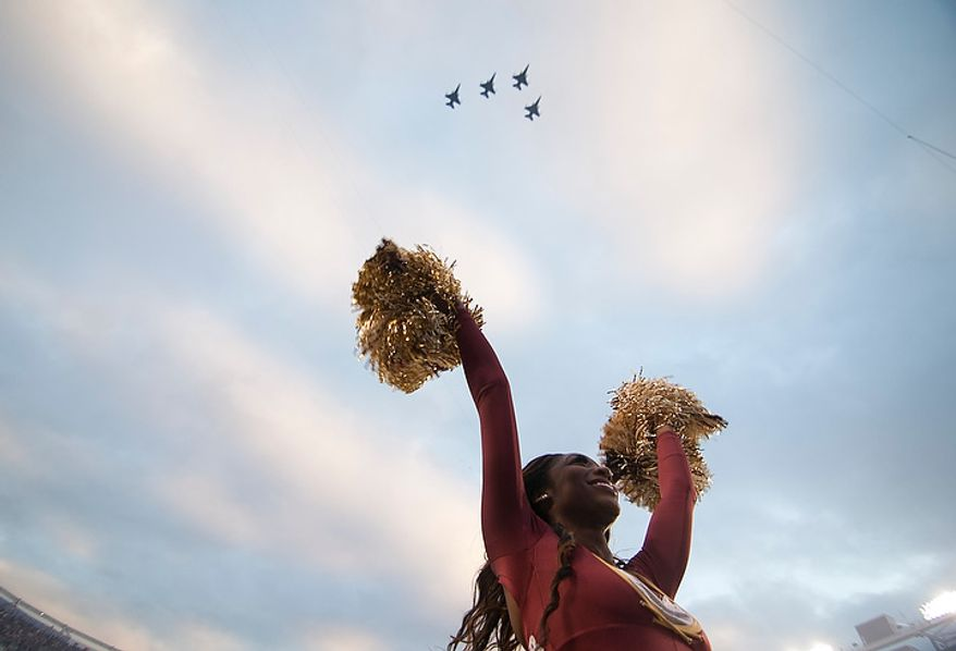 Washington Redskins cheerleader cheers as F-16's fly over before the start of the Washington Redskins against the Seattle Seahawks in the NFC wild card game at FedEx Field, Landover, Md., Sunday, January 6, 2013. (Craig Bisacre/The Washington Times)