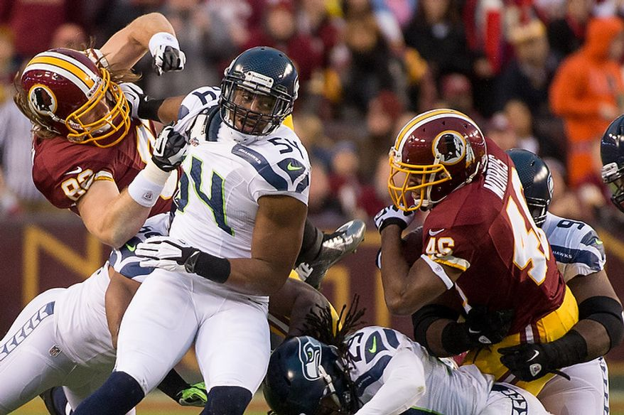 Washington Redskins running back Alfred Morris (46), right, runs for a 9 yard gain in the first quarter as the Washington Redskins play the Seattle Seahawks during the NFC wild card game at FedEx Field, Landover, Md., Sunday, January 6, 2013. (Andrew Harnik/The Washington Times)