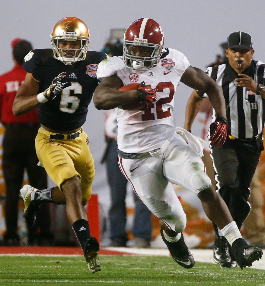 Alabama's Eddie Lacy (42) runs past Notre Dame cornerback KeiVarae Russell during the second half of Alabama's 42-14 win in the BCS National Championship college football game in Miami on Jan. 7, 2013. (Associated Press)