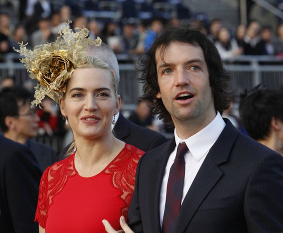 British actress Kate Winslet arrives with her then-boyfriend, Ned Rocknroll, at the awards presentation of The Longines Hong Kong Cup horse race at the Shatin race track in Hong Kong on Sunday, Dec. 9, 2012. (AP Photo/Kin Cheung)