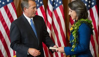Rep. Tulsi Gabbard, Hawaii Democrat, is greeted by Speaker of the House John A. Boehner, Ohio Republican, for the re-enactment of her swearing-in Thursday on the first day of the 113th Congress. Ms. Gabbard is the first Hindu in Congress. (Andrew Harnik/The Washington Times)