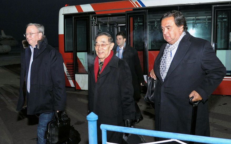 Eric Schmidt (left), executive chairman of Google, and former New Mexico Gov. Bill Richardson (right) arrive in Pyongyang, North Korea, on Monday, Jan. 7, 2013. Mr. Schmidt wants a first-hand look at North Korea's economy and social media in his private visit to the communist nation, his delegation said, despite misgivings in Washington over the timing of the trip. The man in the center was not identified. (AP Photo/Kyodo News)