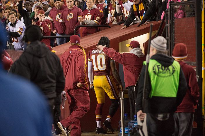 Medical staff members take Griffin into a sideline training room to look at his injured knee late in the fourth quarter Sunday. Coach Mike Shanahan said Monday the extent of the injury remains unknown. (Andrew Harnik/The Washington Times)