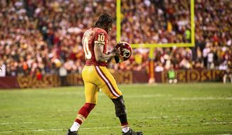 Washington Redskins quarterback Robert Griffin III limps back to the huddle after being hit while throwing in the first quarter of the Redskins' 24-14 loss to the Seattle Seahawks in an NFC wild card game at FedEx Field in Landover, Md., on Jan. 6, 2013. (Andrew Harnik/The Washington Times)