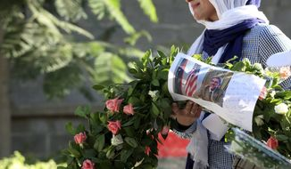 ** FILE ** In this Monday, Sept. 17, 2012, file photo, a Libyan woman, Salwa Bugaighis, carries a wreath with a photo of U.S. Ambassador Chris Stevens on it as she and others gather to pay their respect to the victims of the Tuesday, Sept. 11, 2012, attack on the U.S. Consulate, in Benghazi, Libya. A man linked to the attack on the U.S. Consulate in Benghazi has been conditionally released by Tunisian authorities due to lack of evidence, his lawyer said Tuesday Jan. 8, 2013. (AP Photo/Mohammad Hannon, File)