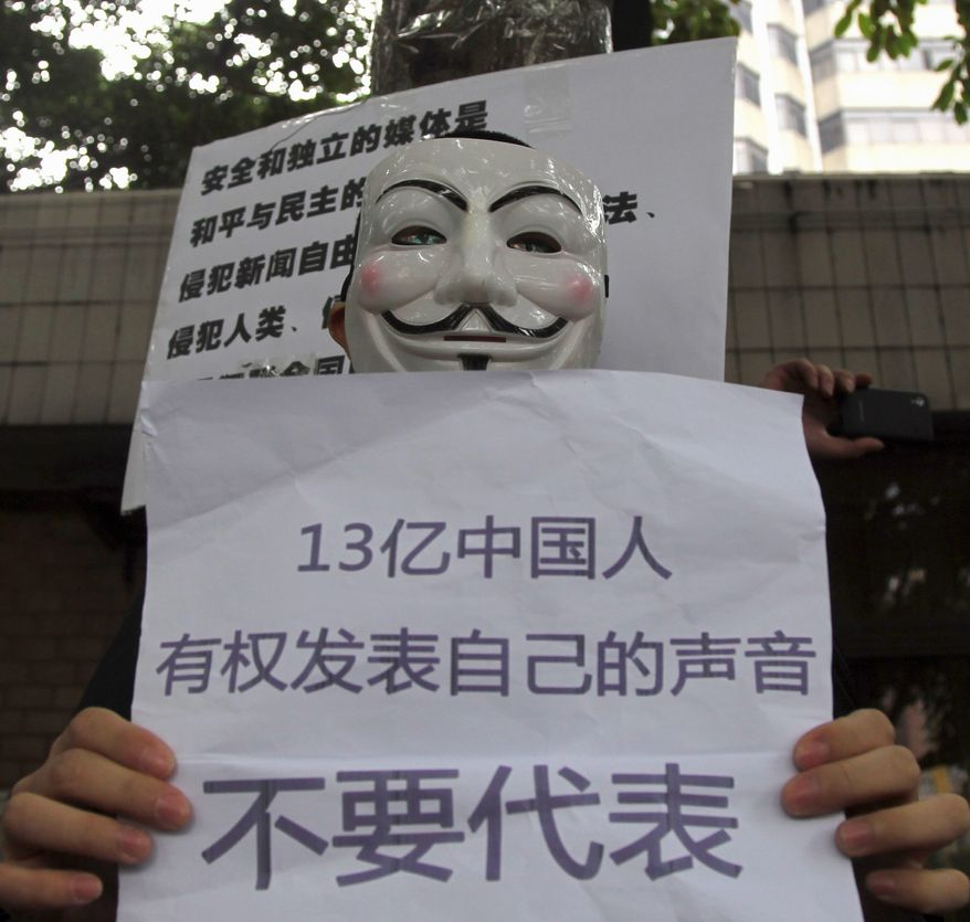 "A supporter of the Southern Weekly protests in Guangzhou with a banner that translates as ""1.3 billion Chinese have rights to their own voice and do not want to be represented."" (Associated Press)"
