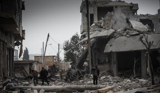 **FILE** Syrians inspect the destruction of buildings on Jan. 5, 2013, after heavy shelling by the Syrian Air Force in apparent retaliation for rebel attacks on the nearby Taftanaz military airbase in the village of Binnish, Syria. (Associated Press)