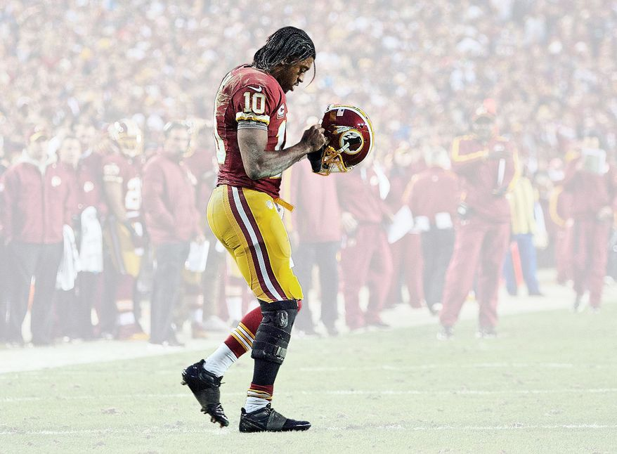 Washington Redskins quarterback Robert Griffin III returns to the huddle after hurting his right knee as he fell awkwardly while throwing an incomplete pass during the first quarter of their NFL wild card playoff football game against the Seattle Seahawks in Landover, Md.., on Jan. 6, 2013. (Associated Press/The Virginian-Pilot)