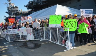 Family and friends of the crew of the aircraft carrier USS Dwight D. Eisenhower await pierside at Naval Station Norfolk on Dec. 12, 2012, as the ship approaches after a six-month deployment. (U.S. Navy/Mass Communication Specialist 1st Class Julie Matyascik)