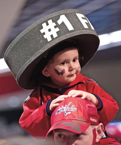 Aiden Witmer, 2, of Alexandria, Va., sits on the shoulders of his dad, Josh, on the way to their seats before the Washington Capitals take on the Boston Bruins in game four of National Hockey League first round playoff hockey at the Verizon Center in Washington on April 19, 2012. (Andrew Harnik/The Washington Times)