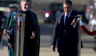 Defense Secretary Leon E. Panetta (right) motions Afghan President Hamid Karzai to the viewing stand during a full-honors arrival ceremony Thursday on the River Parade Field at the Pentagon. (Associated Press)