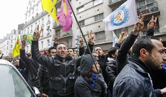 Kurds demonstrate on Thursday, Jan. 10, 2013, in front of a pro-Kurdish center in Paris where three Kurdish women were killed in what the French interior minister called an execution. (AP Photo/Remy de la Mauviniere)