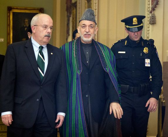 Afghanistan President Hamid Karzai, is escorted by Sergeant of Arms of the Senate Terrance Gainer, left, as he walks to a meeting with U.S. senators on Capitol Hill in Washington, Wednesday, Jan. 9, 2013. (AP Photo/Manuel Balce Ceneta)