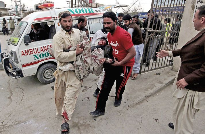 Volunteers rush an injured victim to a hospital after two bomb blasts about five minutes apart killed 81 Thursday night at a billiard hall in Quetta, Pakistan. (Associated Press)