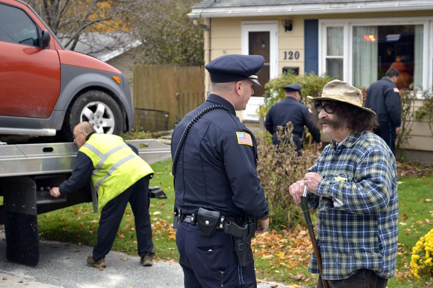 Television movie critic Gene Shalit (right) talks with a police officer after crashing his car into a house on Housatonic Street in Lenox, Mass., on Wednesday, Oct. 24, 2012. (AP Photo/The Berkshire Eagle, Ben Garver)