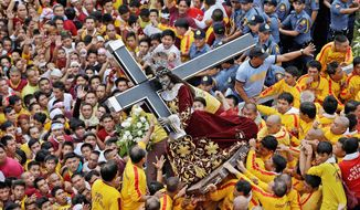 Catholic devotees jostle near the centuries-old image of the Black Nazarene on its feast day Wednesday in Manila. The Catholic Church no longer sways the masses on issues such as birth control as it once did. (Associated Press)