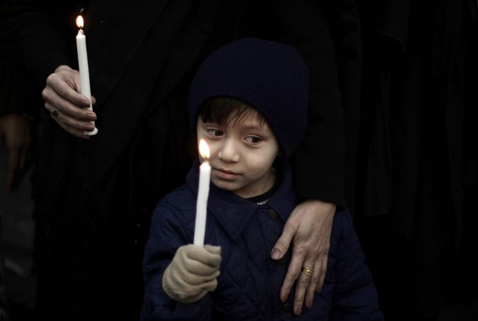 A Pakistani boy holds a candle while he and his mother take part in a Jan. 11, 2013, protest in Islamabad, Pakistan, to condemn deadly bombings in Quetta the previous day. Shiites in a southwestern Pakistani city hit by a brutal terror attack refused to bury their dead Friday in protest, demanding that the government do something to protect them from what has become a barrage of bombings and shootings against the minority Muslim sect. (Associated Press)
