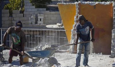 Edner Gue (right) and Labon Florestal work to clean up the earthquake damaged Grande College Auguste Comte de Petionville, in their neighborhood of Petionville, Haiti, on Jan. 11, 2013. The director of the elementary and high school is paying workers to clean up his school and plans to open classes even if the government does not rebuild it. On Jan. 12, Haiti will mark the 3rd anniversary of the earthquake that officials say killed more than 300,000 people and displaced more than a million others. The disaster is regarded as one of the worst natural disasters in modern history. (Associated Press)