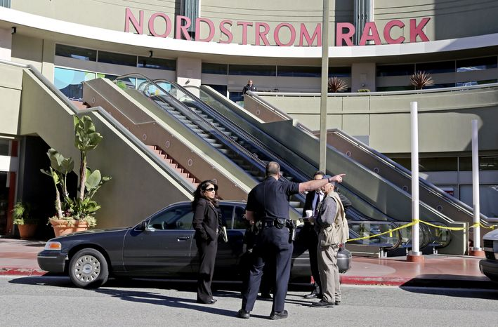 Los Angeles police investigators stand outside a Nordstrom Rack store at Howard Hughes Center near Los Angeles International Airport Friday, Jan. 11, 2013. Robbers stabbed a clothing store employee and sexually assaulted another during an hours-long hostage drama that ended early Friday with a police SWAT team surging into the shop and rescuing 14 workers. (AP Photo/Reed Saxon)