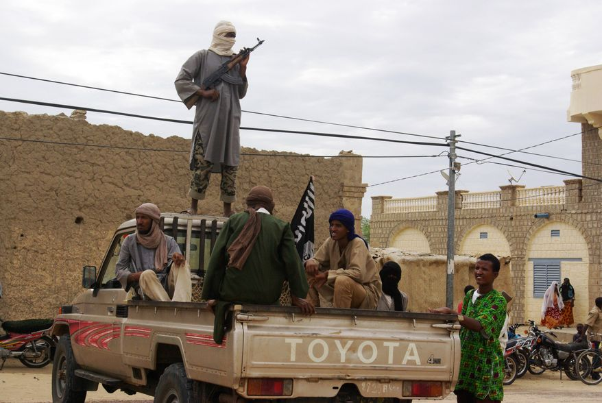 **FILE** Fighters from Islamist group Ansar Dine stand guard Aug. 31, 2012, in Timbuktu, Mali, as they prepare to publicly lash a member of the Islamic Police found guilty of adultery. (Associated Press)