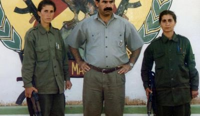 **FILE** In this early 1990s photo, Sakine Cansiz (left), one of the founders of a militant group battling Turkish troops since 1984, and another woman surround Abdullah Ocaln, leader of the Kurdistan Workers Party, or PKK, at the Mahzun Korkmaz rebel camp in the Bekaa Valley, Lebanon. (Associated Press/IHA)