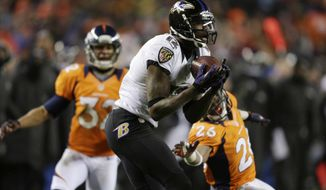 Baltimore Ravens wide receiver Jacoby Jones (12) catches a touchdown pass as Denver Broncos free safety Rahim Moore (26) and Denver Broncos defensive back Tony Carter (32) defend in the fourth quarter of an AFC divisional playoff NFL football game, Saturday, Jan. 12, 2013, in Denver. (AP Photo/Joe Mahoney)