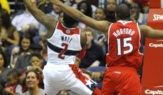Washington Wizards guard John Wall (2) drives in for two points away from the defense of Atlanta Hawks forward Al Horford (15) during the second half of their NBA basketball game on Saturday, Jan. 12, 2013, in Washington. The Wizards defeated the Hawks 93-83. (AP Photo/Richard Lipski)