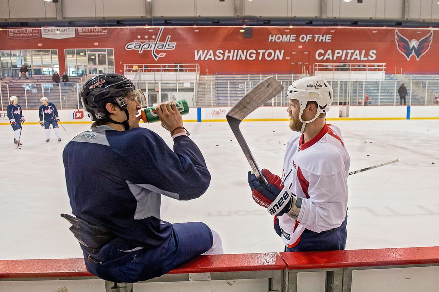 Capitals left wing Alex Ovechkin (left) and defenseman John Erskine take a break during a team workout at Kettler Iceplex on Tuesday. Sunday marked the first day of training camp at Kettler, with the season opening at Tampa Bay on Saturday. (Andrew Harnik/The Washington Times)