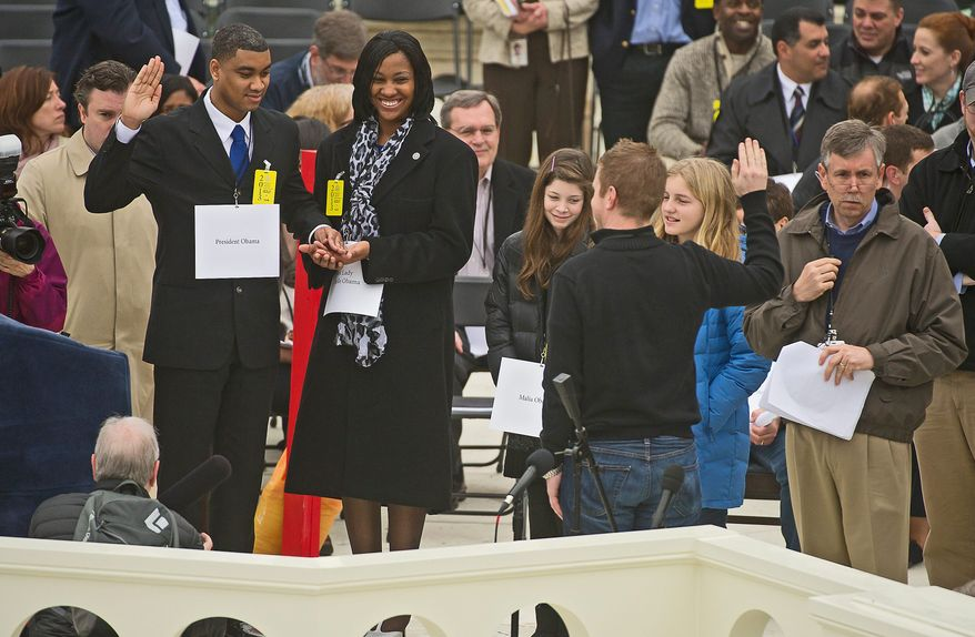 Air Force Staff Sgt. Serpico D. Elliott and Army Spc. Delandra Rollins stand in Sunday for President Obama and first lady Michelle Obama at the rehearsals on the West Lawn of the Capitol. Meanwhile, window washers restore the gleam of the Newseum in anticipation of the festivities. (Associated Press)
