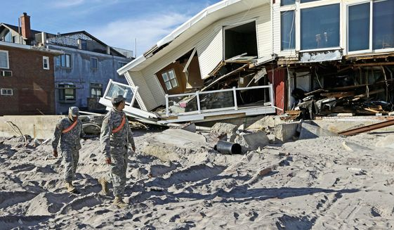 National Guardsmen Spc. Ivan Pimentel (left) and Pfc. Harry Cadet walk past a house on the beach in the Rockaways on New York's Long Island on Thursday that was ravaged by Superstorm Sandy in October. They were going door-to-door to determine if residents needed portable heaters or other items in the wake of Sandy. (Associated Press)