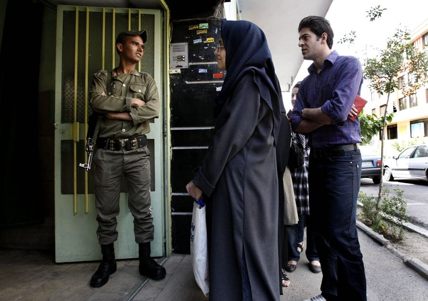 ** FILE ** In this Friday, June 12, 2009, photo, an Iranian police officer stands guard as people line up outside a polling station in Tehran, Iran. (AP Photo/Vahid Salemi)
