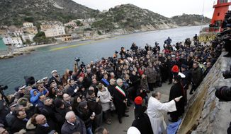 A priest blesses a commemorative plaque bearing the names of the 32 people who died in the Costa Concordia shipwreck after the plaque was unveiled on Tuscany's Isola del Giglio on Sunday, Jan. 13, 2013. Survivors of the shipwreck and relatives of those who died marked the first anniversary of the grounding Sunday. (AP Photo/Gregorio Borgia)