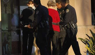 Police officers talk with a witness near a shooting at the Reading Cinemas in San Diego on Saturday evening, Jan. 12, 2013. Police shot and critically wounded a man suspected of chasing his girlfriend with a handgun after they found him hiding inside the movie theater. It was the second shooting at a San Diego County movie theater in as many days. (AP Photo/UT San Diego, Earnie Grafton)