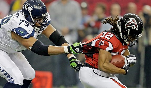Seattle Seahawks' Red Bryant (79) tries to stop Atlanta Falcons' Jacquizz Rodgers (32) during the first half of an NFC divisional playoff NFL football game Sunday, Jan. 13, 2013, in Atlanta. (AP Photo/David Goldman)
