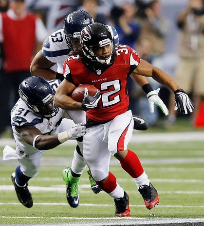 Atlanta Falcons running back Jacquizz Rodgers (32) works against Seattle Seahawks outside linebacker Malcolm Smith (53) and strong safety Kam Chancellor (31) during the second half of an NFC divisional playoff NFL football game Sunday, Jan. 13, 2013, in Atlanta. (AP Photo/John Bazemore)