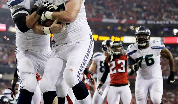 Seattle Seahawks outside linebacker K.J. Wright (50) picks up the ball after Marshawn Lynch scored a touchdown  during the second half of an NFC divisional playoff NFL football game against the Atlanta Falcons Sunday, Jan. 13, 2013, in Atlanta. (AP Photo/David Goldman)