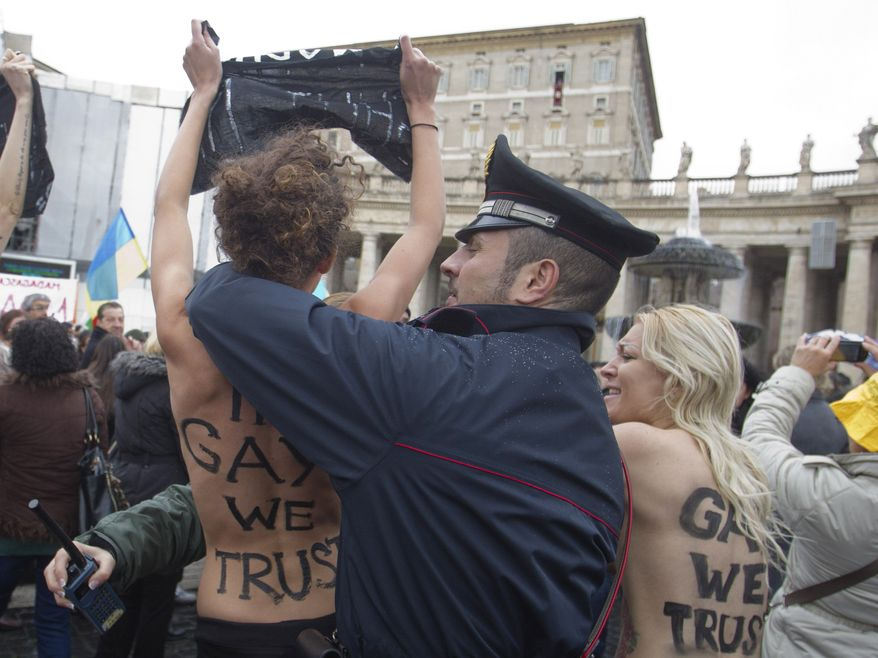 """Police officers stop members of a group of four women who went topless to protest the Vatican's opposition to gay marriage in St. Peter's Square at the Vatican on Sunday, Jan. 13, 2013. Police quickly took the women away, and the pope appeared not to have been disturbed as he delivered his traditional prayer from his studio window overlooking the piazza. On their bare backs, the women had painted the slogans """"In Gay We Trust"""" and """"Shut Up. (AP Photo/Angelo Carconi)"""