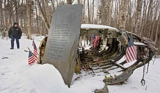Police Chief Jeff Pomerleau views a monument next to wreckage from a B-52 bomber on Elephant Mountain near Greenville, Maine. The 40-foot-tall vertical stabilizer had snapped off and the plane crashed on Jan. 24, 1963, killing seven onboard. (Associated Press)