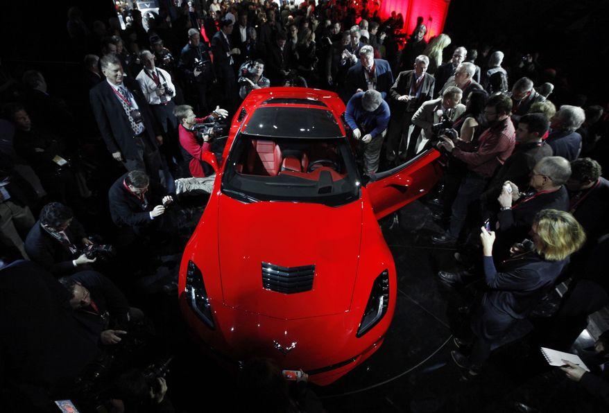 Journalists surround General Motors' 2014 Chevrolet Corvette Stingray on Sunday, Jan. 13, 2013, the night before press days at the North American International Auto Show in Detroit. (AP Photo/Paul Sancya)