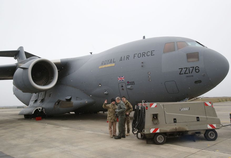 A French airman (center) talks with British military personnel at the French army base in Evreux, 56 miles north of Paris, on Monday, Jan. 14, 2013, before the takeoff the British C17 transport plane en route to Mali. British military equipment was readied for deployment in Mali on Monday as international intervention in the African country increased following advances in the north by Islamic extremists with reported links to al Qaeda. (AP Photo/Michel Euler)