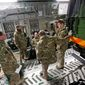 British soldiers gather next to a French army truck inside a British transport plane at a base in Evreux on Monday, part of Britain's authorization over the weekend to send two C-17 transport planes to help France get more troops to Mali. (Associated Press)