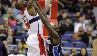 Washington Wizards center Emeka Okafor (50) shoots over Orlando Magic forward Andrew Nicholson in the first half of the Wizards' 120-91 win on Jan. 14, 2013 in Washington. (Associated Press)