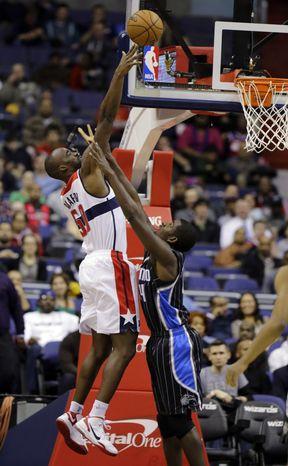 Washington Wizards center Emeka Okafor (50) shoots over Orlando Magic forward Andrew Nicholson in the first half of the Wizards' 120-91 win on Jan. 14, 2013 in Washington. (Associated Press)
