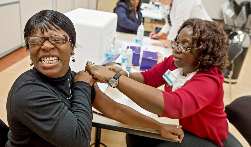 Rochelle Claitt, visiting from Hopkinsville, Ky., looks none too happy while getting a free flu shot Tuesday from nurse Gloria Oniha at Laurel Regional Hospital. Supplies of the vaccine are running low in some particularly hard-hit areas. (Associated Press)