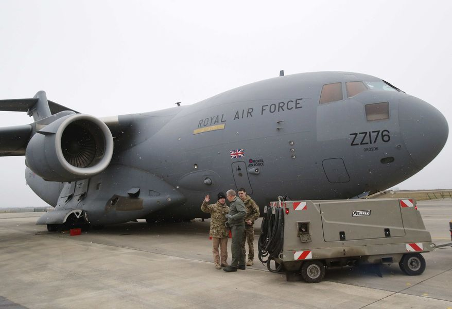 A French airman, center, talks to British military personnel prior to the take off a British C17 transport plane enroute to Mali at the French army base in Evreux, 90 kms (56 mls )north of Paris, Monday, Jan. 14, 2013. (AP Photo/Michel Euler)