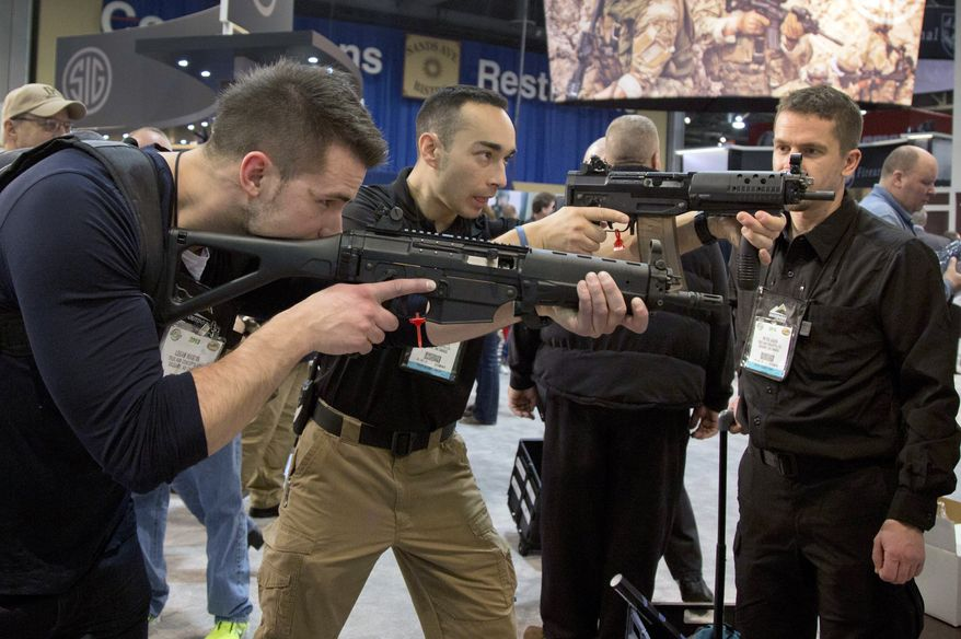 ** FILE ** Firearms instructors Logan Martin (left) and Andres Gonzalez of Calgary, Alberta, look through the sights of Sig Sauer Swat Patrol AR rifles during the 35th annual SHOT Show on Tuesday, Jan. 15, 2013, in Las Vegas. (AP Photo/Julie Jacobson)
